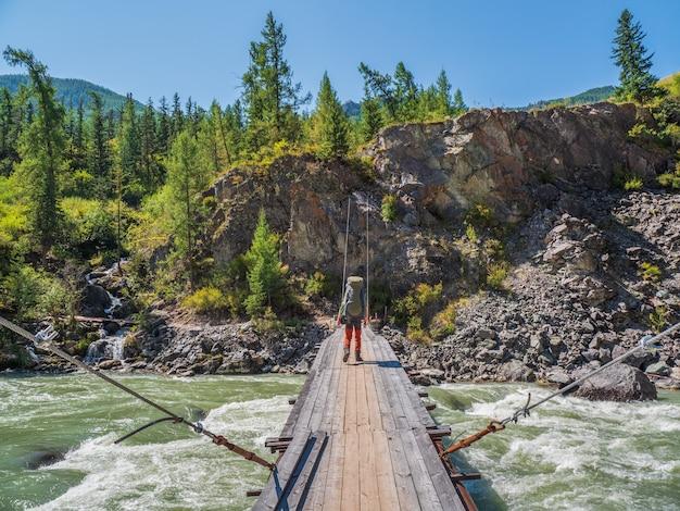 Turismo masculino com uma grande mochila verde caminha ao longo de uma velha ponte de madeira no contexto de uma floresta de coníferas e montanhas à distância.