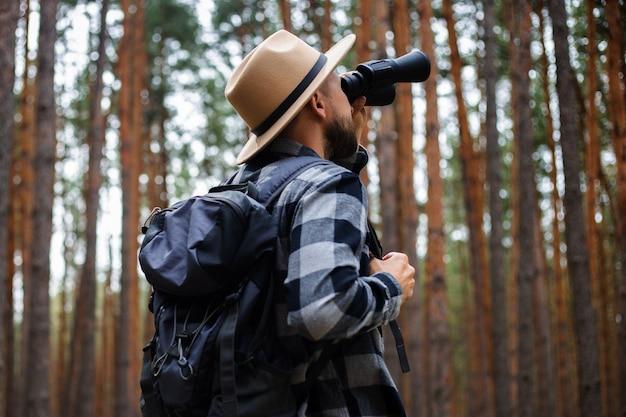 Turismo masculino olhando através de binóculos na floresta.