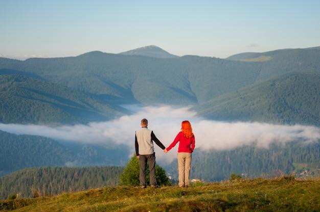 Turismo masculino segurando as mãos garota ruiva de pé sobre uma colina