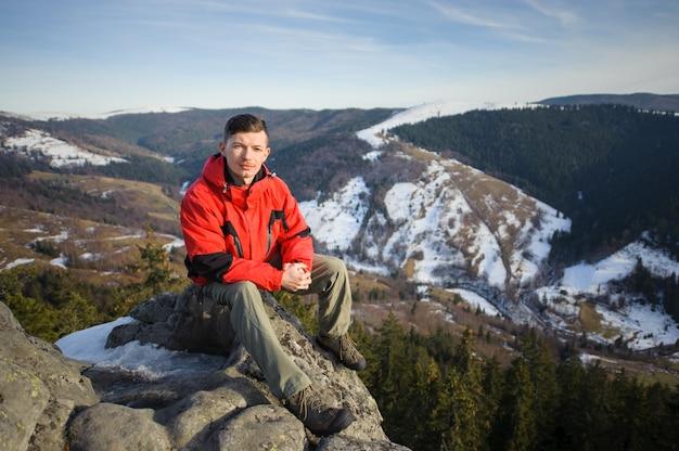 Turismo masculino sentado na rocha no topo da montanha
