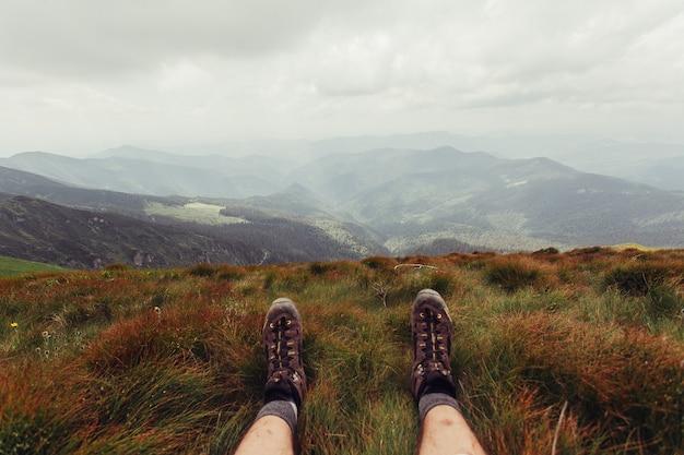 Turismo, montanhas, estilo de vida, natureza, conceito de pessoas - pernas masculinas nos sapatos marrons deitado na montanha no fundo da paisagem do mar