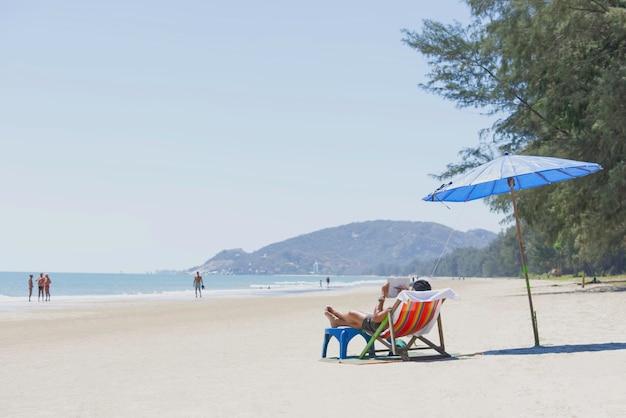Turismo na cama de lona e guarda-chuvas na praia fundo turismo embaçado e mar na praia de suan son pradipat, prachuap khiri khan na tailândia. 16 de fevereiro de 2020