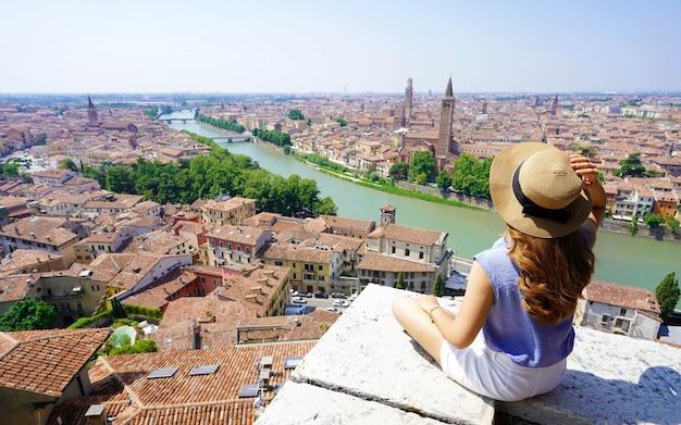 Turismo na itália. mulher jovem e bonita sentada na parede, apreciando a vista deslumbrante de verona, itália.
