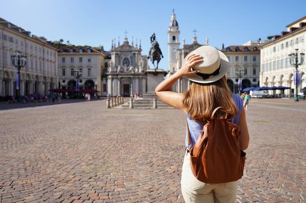 Turismo na itália. vista traseira da garota turista visitando a praça san carlo, em turim, itália. mochileiro feminino jovem visitando a europa.