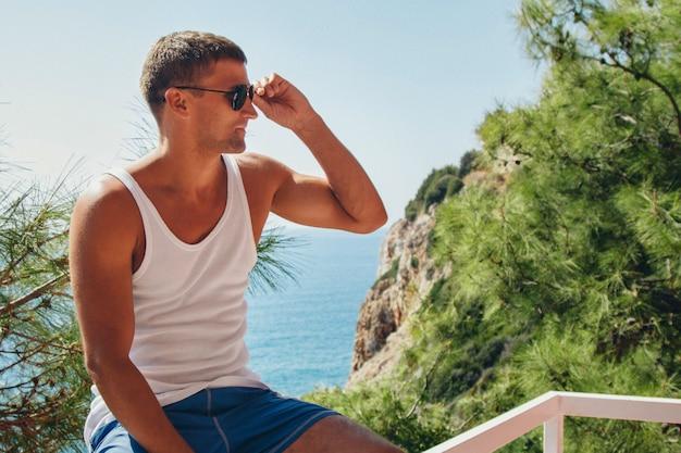 Turismo, o lazer é um homem bonito, se aquecendo no vestido branco na varanda do hotel com vista para plantas tropicais e mar