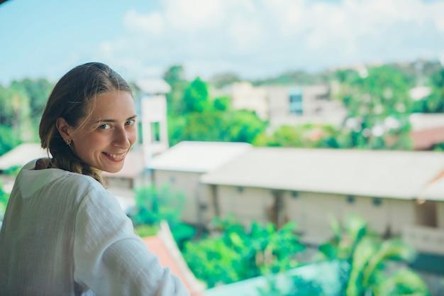 Turismo, o lazer é uma menina bonita com cabelos longos, se aquecendo no vestido branco na varanda do hotel, com vista para plantas tropicais e um pequeno prédio