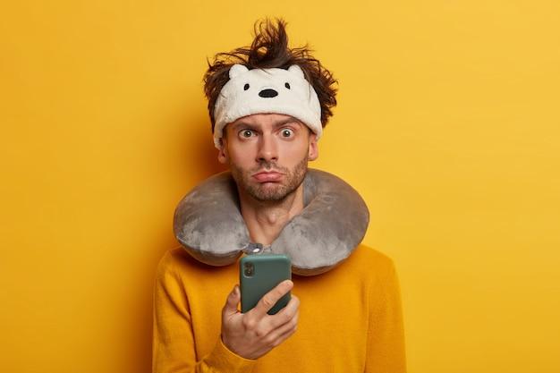 Turismo, tecnologia e conceito de viagem. viajante descontente do sexo masculino usa telefone celular, verifica o tempo, cansado da longa viagem, acorda no meio do transporte