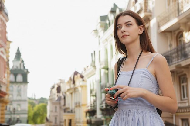 Turismo turístico feminino bonito na cidade, andando com uma câmera vintage