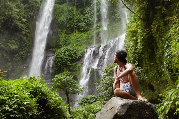 Turismo, viagens e aventura. jovem hippie estiloso sentado na pedra com os pés descalços e virando a cabeça para trás para ver uma cachoeira incrível