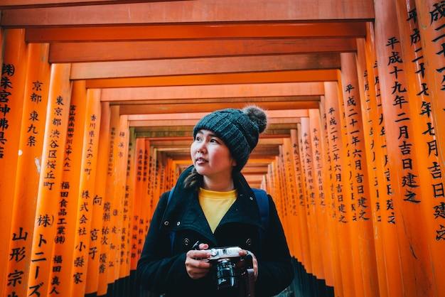 Turista admirando a estrutura do santuário fushimi inari taisha em kyoto, japão