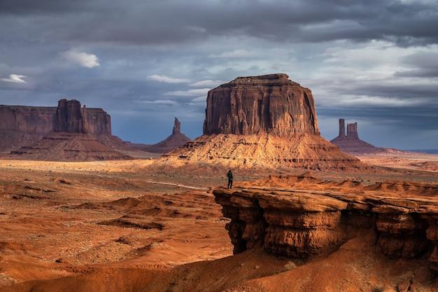 Turista admirando a vista com a tempestade ao fundo no monument valley