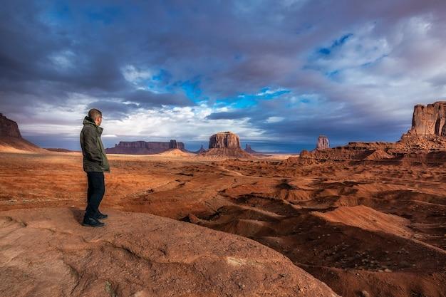 Turista admirando a vista com tempestade no fundo em monument valley, arizona, eua.