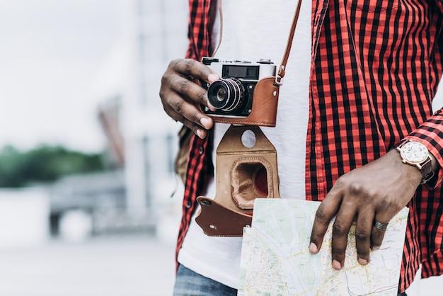 Turista afro-americano bonito e feliz com câmera antiga e mapa na cidade moderna