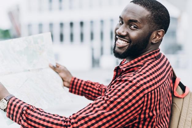 Turista afro-americano bonito e feliz com mapa na cidade moderna