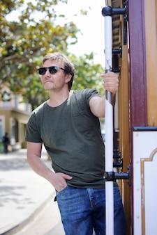 Turista alegre masculina que toma um passeio no teleférico famoso em san francisco, califórnia, eua.
