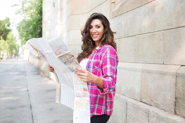 Turista alegre usando o mapa de papel na cidade estranha