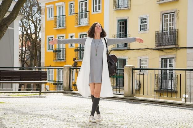 Turista animada posando na cidade velha