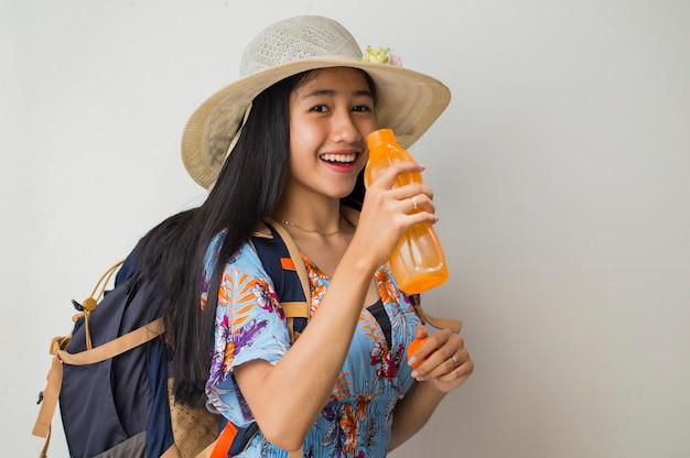 Turista asiática com mochila bebendo água no fundo branco