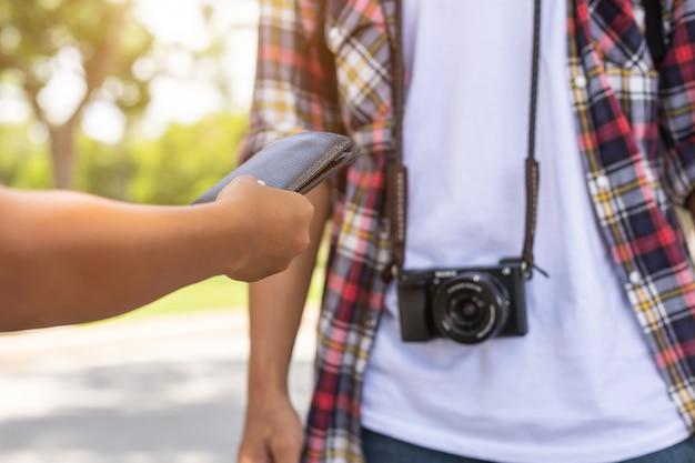 Turista asiática pegando sua carteira preta de outras pessoas que encontraram em atração turística