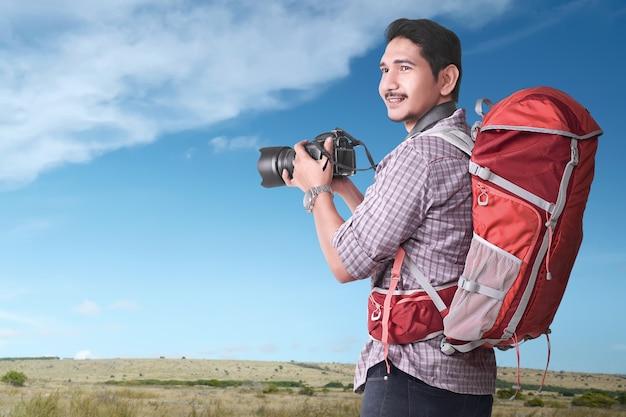 Turista asiática sorridente com mochila e câmera