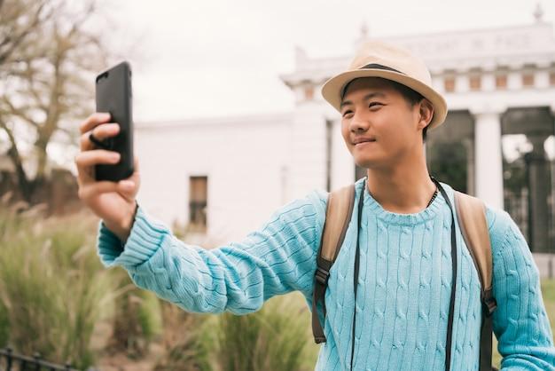 Turista asiática tirando uma selfie com o celular.