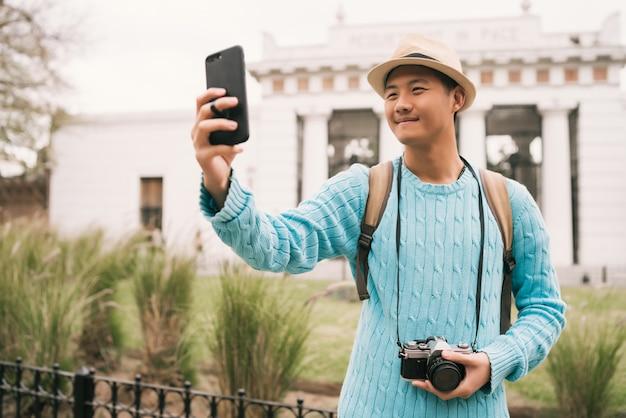 Turista asiática tomando uma selfie com telefone móvel