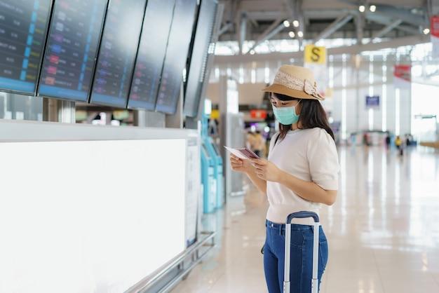 Turista asiática usando máscara facial, verificando o voo no painel de embarque