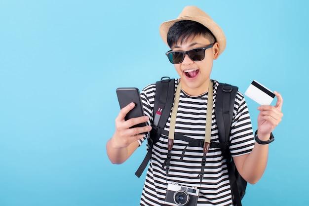 Turista asiático está feliz e mostra seu cartão de crédito e paga com cartão