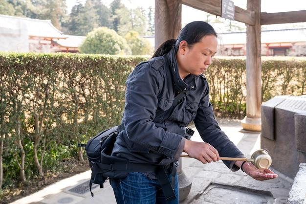 Turista asiático pegando um santuário de água benta para lavar as mãos antes de entrar no templo todaiji, prefeitura de nara, japão