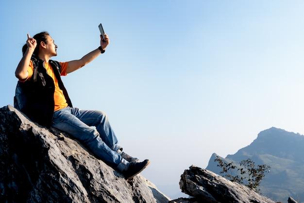 Turista asiático sentado no ponto mais alto da montanha rochosa e usando um telefone celular
