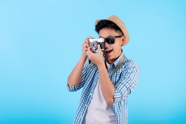 Turista asiático, sorrindo e tirando fotos em um fundo azul