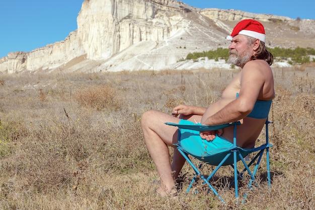 Turista barbudo com calção de praia e chapéu de papai noel relaxando em uma área montanhosa rochosa no verão