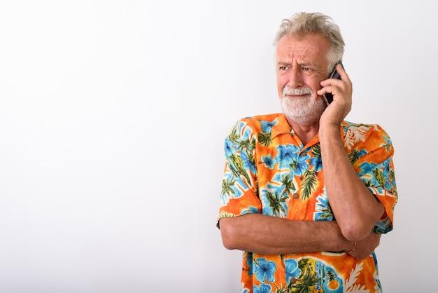 Turista barbudo sênior parecendo estressado enquanto pensa e fala no celular em branco