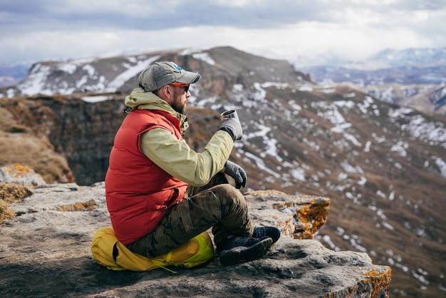 Turista bebendo chá em um fundo de montanhas