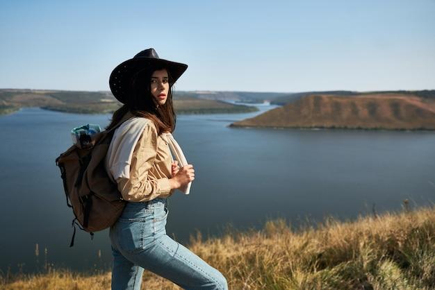 Turista bonita com chapéu de cowboy caminhando com mochila ao ar livre