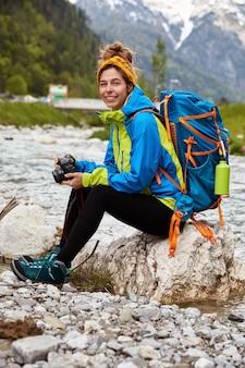 Turista cansada sentada em pedras perto de um riacho nas montanhas, segura uma câmera profissional, vê fotos