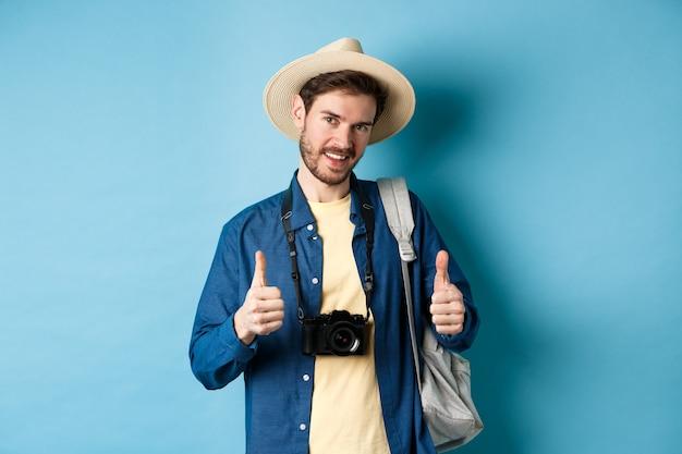 Turista caucasiana bonita com chapéu de palha, segurando a mochila e a câmera fotográfica, mostrando os polegares para cima, recomendando a agência de viagens ou resort, fundo azul.