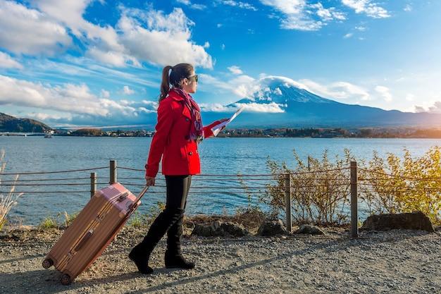 Turista com bagagem e mapa na montanha fuji, kawaguchiko, no japão.