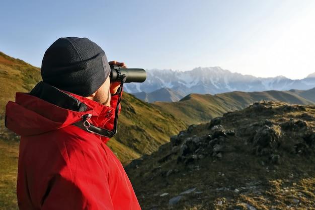 Turista com binóculos olhando em uma área montanhosa