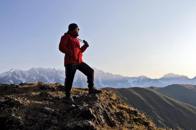 Turista com binóculos olhando em uma montanha