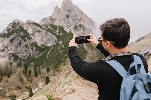 Turista com cabelo preto curto admira montanhas italianas e tira foto em smartphone