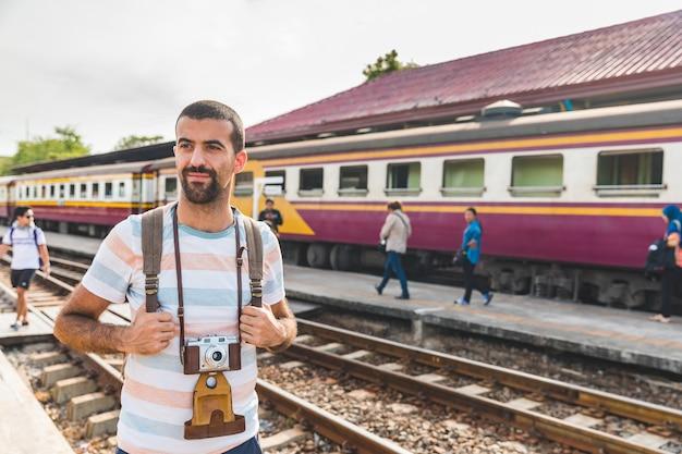 Turista com câmera na estação de trem na tailândia