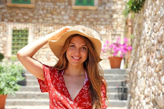 Turista com chapéu e vestido vermelho posando em uma aconchegante rua italiana em taormina, sicília