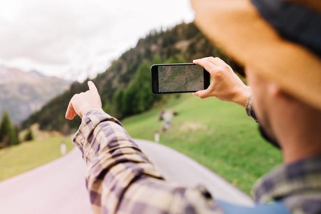 Turista com chapéu marrom claro indo para os alpes e usando navegador para evitar se perder
