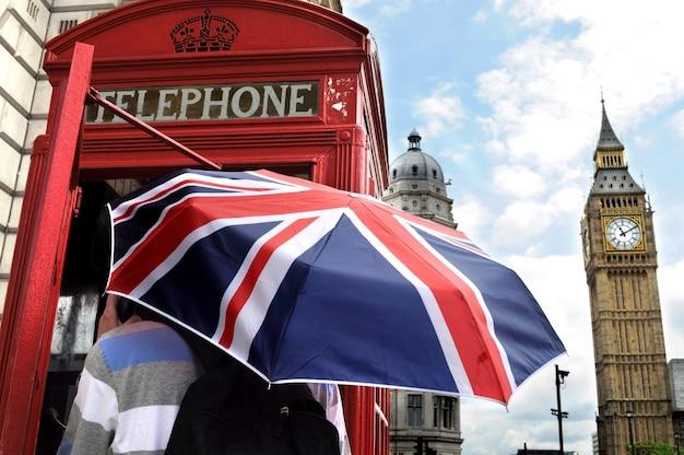 Turista com guarda-chuva britânico na caixa de telefone em londres