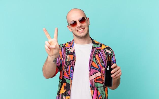 Turista com homem de turista de cerveja sorrindo e parecendo amigável, mostrando o número dois ou o segundo com a mão para a frente, em contagem regressiva