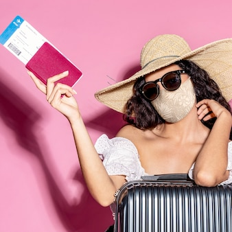 Turista com máscara facial com passaporte e bagagem