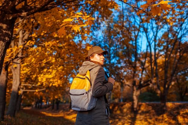 Turista com mochila andando na floresta de outono. jovem mulher viajar ao pôr do sol