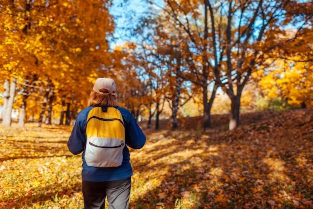 Turista com mochila andando na floresta de outono