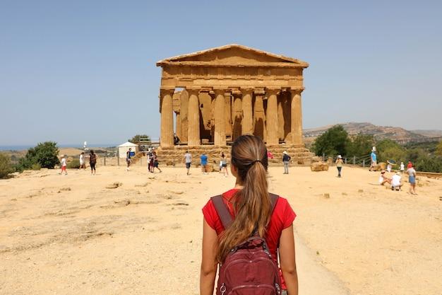 Turista com mochila visitando o templo da concórdia na sicília, itália